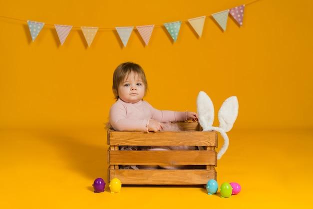 핑크 드레스에 여자 아기는 노란색 바탕에 화려한 계란 나무 상자에 앉는 다.