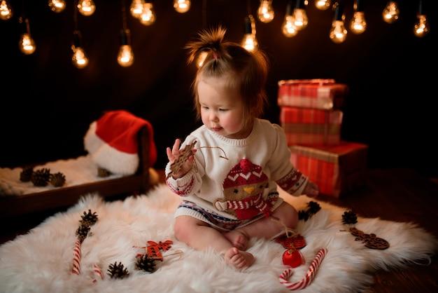 Девочка в красном новогоднем костюме с ретро-гирляндами сидит на меху