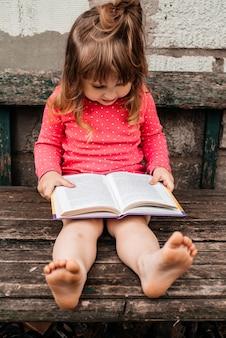 緑の草の上に赤で、晴れた夏の日に本を読んでいる女の赤ちゃん。