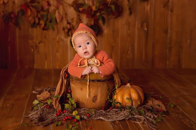 Девочка в осеннем декоре с тыквами, ягодами и листьями на день благодарения или хэллоуин
