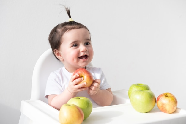 白でリンゴを食べる赤ちゃんの椅子の女の赤ちゃん