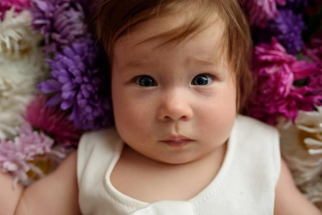 ピンクのチューリップの束で遊んで青いドレスの女の赤ちゃん。日当たりの良い保育園で自宅で小さな子供。花を楽しんでいる幼児