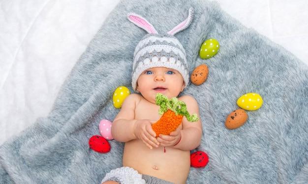 Девочка в шляпе кролика лежит на сером одеяле с разноцветными пасхальными яйцами и морковью в руках
