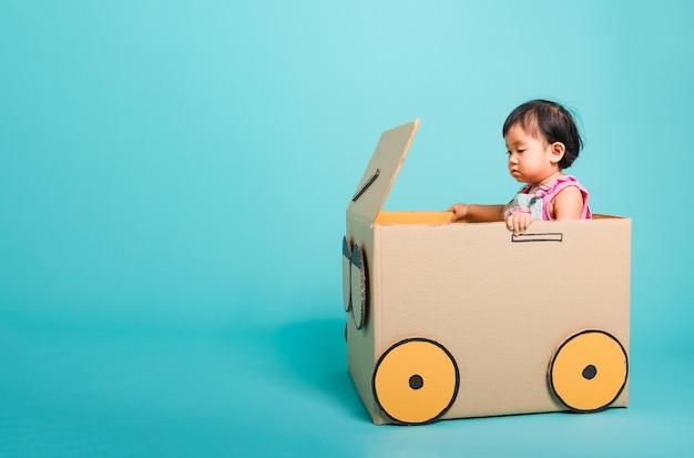 段ボール箱で作られた車の中で女の赤ちゃん