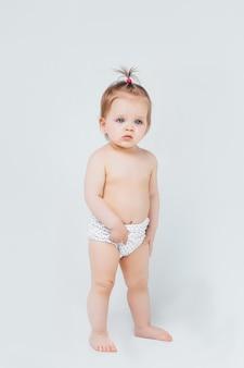 흰 벽에 행복한 미소를 짓고 앉아 기저귀에 아기 소녀