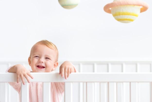 彼女のベビーベッドの女の赤ちゃん