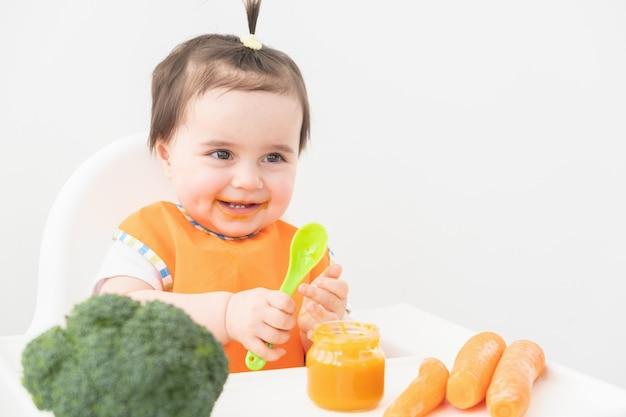 白い背景の上の野菜のピューレを食べるチャイルズの椅子に座っているオレンジ色のよだれかけの女の赤ちゃん。