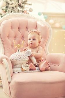 분홍색 옷과 복고 스타일의 행복한 인테리어에 여자 아기