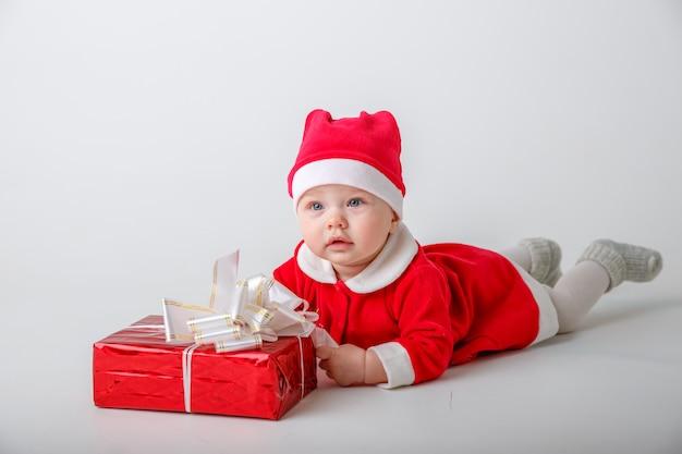 흰색 배경에 새 해 선물 산타 클로스 의상을 입은 여자 아기