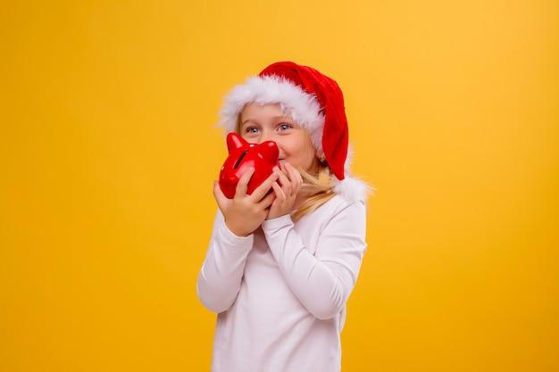 Девочка в новогодней шапке держит красную копилку на желтой стене, место для текста