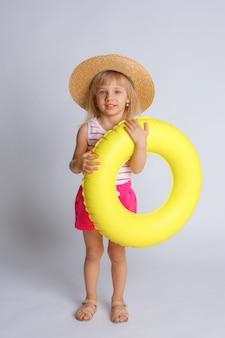夏服と白い背景の水泳サークルの女の赤ちゃん。夏休みのコンセプト