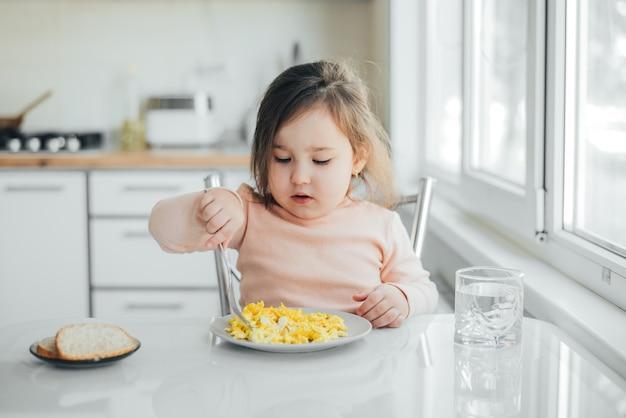 오믈렛을 먹고 분홍색 스웨터에 흰색 빛 부엌에서 오후에 아기 소녀