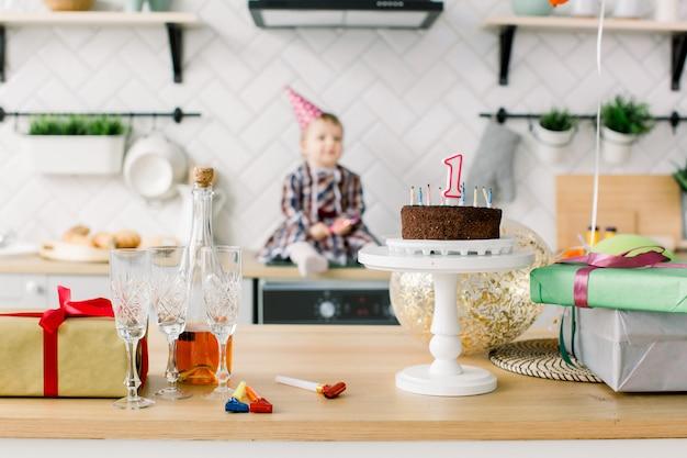 台所で女の赤ちゃん。赤ちゃんの最初の誕生日。風船と誕生日ケーキで誕生日パーティーを祝う美しい少女。一年パーティー。ピンクの誕生日帽子でかわいい幼児の女の子。