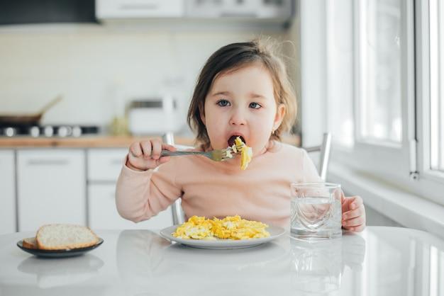오믈렛을 먹고 흰색 분홍색 스웨터에 여자 아기
