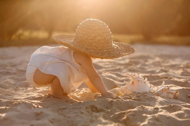 夏の砂浜のビーチで遊んで白い服の女の赤ちゃん