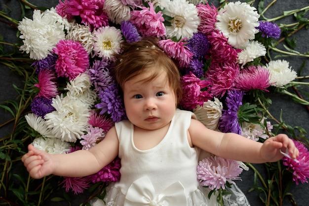 花の束と遊ぶ白いドレスの女の赤ちゃん