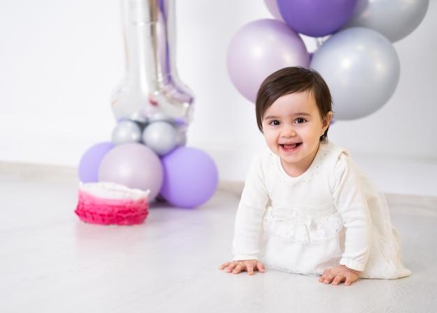 케이크와 풍선으로 그녀의 첫 번째 생일을 축하하는 바닥에 앉아 흰 드레스 아기 소녀.