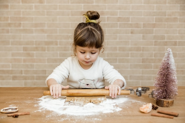 Baby girl is preparing gingerbread in the kitchen.girl with rolling pin,dough and flour