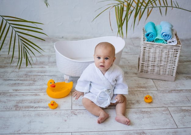 여자 아기는 옆에 세라믹 아기 목욕이 있는 흰색 목욕 가운을 입고 바닥에 앉아 있습니다. 아동 위생