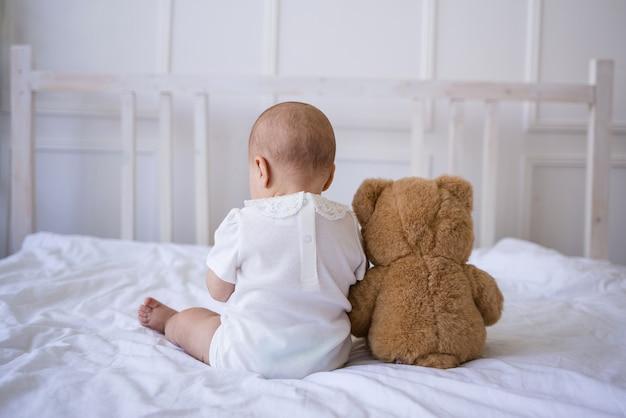 아기 소녀는 테디 베어 장난감을 가지고 침대에 등을 대고 앉아 있습니다