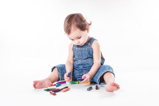 女の赤ちゃんは大きな紙に何かを書いている、それに座っている