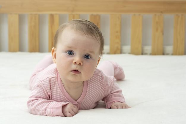 おなかを置く方法を学ぶ女の赤ちゃん。教育と親子関係。