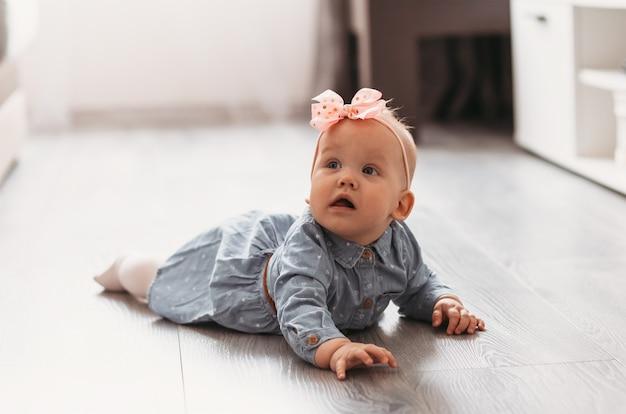 女の赤ちゃんは部屋の床を這うことを学びます。