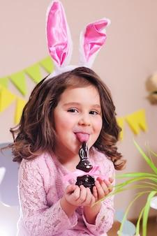 女の赤ちゃんがチョコレートイースターのウサギを舐める