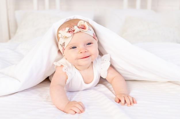 아기 소녀는 담요 아래에 누워 집에 있는 흰색 면 침대에 미소를 짓고 있습니다.