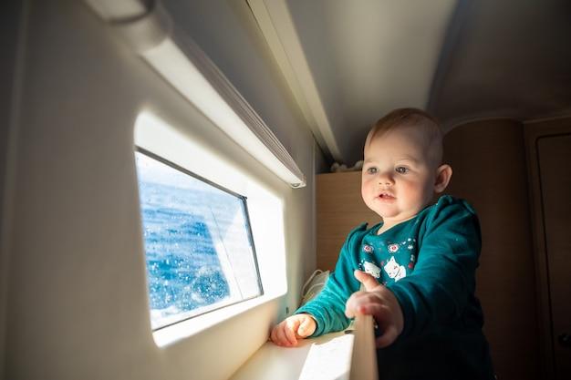 クロアチアの海でヨットに乗っている間、ヨットの窓を見る女の赤ちゃん
