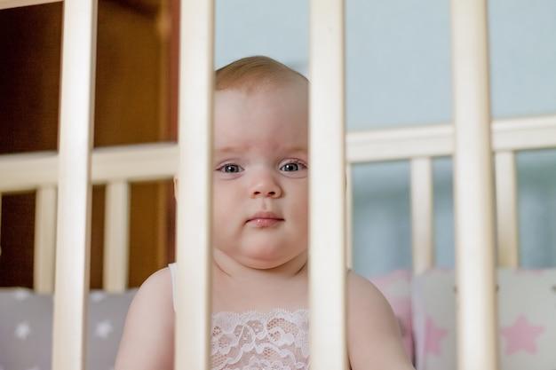 女の赤ちゃんは、ベッドの棒を通して見えます。