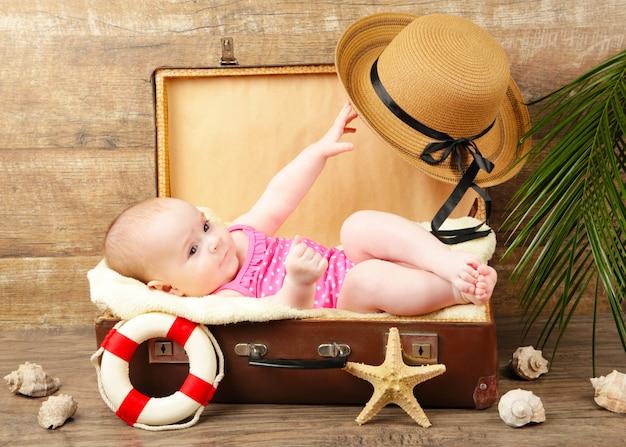 Девочка лежит в чемодане с пляжными аксессуарами на коричневом