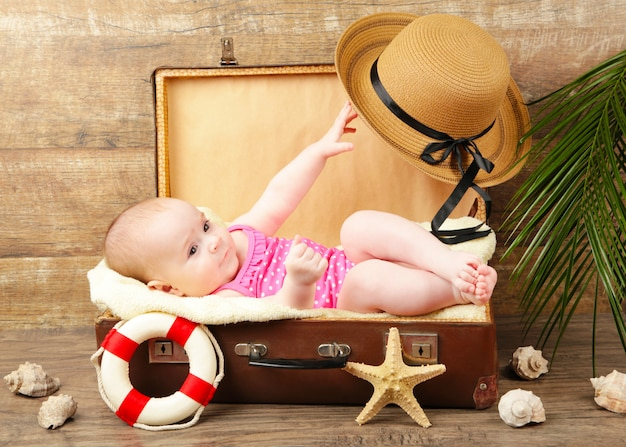 Baby girl lying in a suitcase with beach accessories on brown