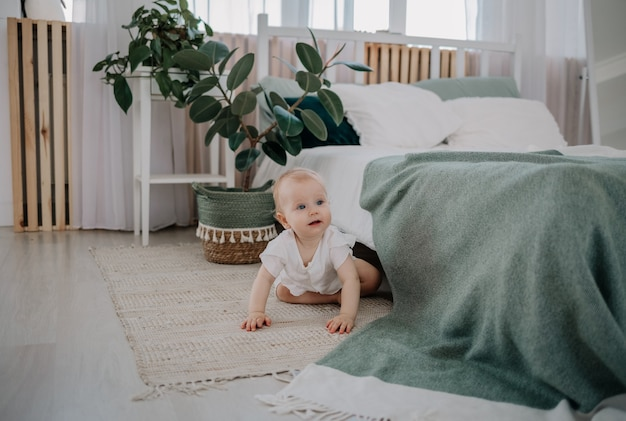 A baby girl in a muslin jumpsuit crawls on the floor in the bedroom