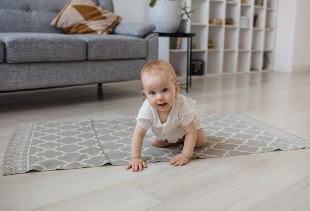 A baby girl in a muslin jumpsuit crawls in a room on a gray rug