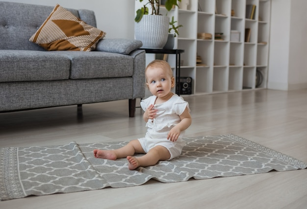 A baby girl in a muslin jumpsuit is sitting in a room on a gray rug