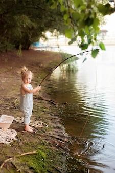 川の近くの砂浜で女の赤ちゃんは釣り竿釣りを保持しています。