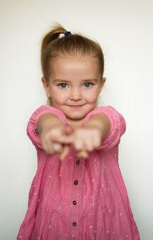 Девочка на белом фоне указывает пальцем на вас