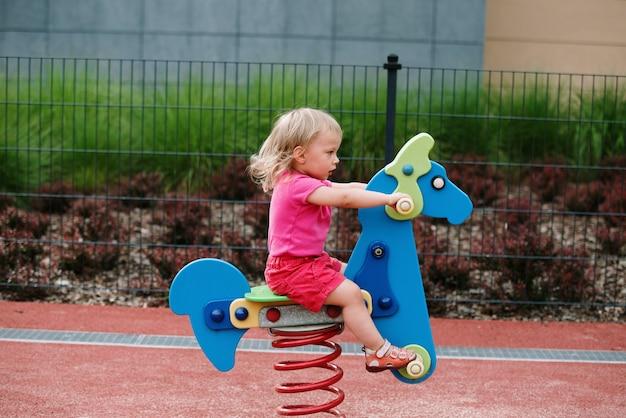 Девочка на детской площадке, верховая езда