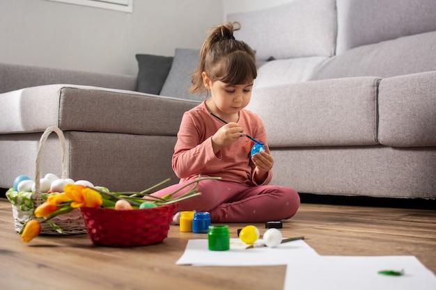 家でイースターエッグを描いている女の赤ちゃん。