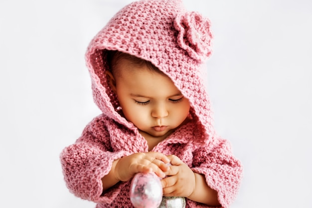 Baby girl in pink romper playing with easter eggs, season holiday concept