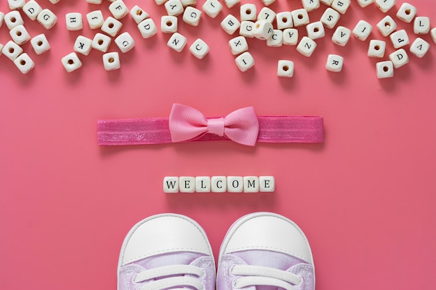Baby girl pink table with newborn shoes, bow and welcome words. baby flat lay.