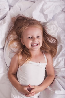 Девочка играет в пижаме на кровати