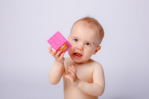 Baby girl playing dice in a diaper on a white background
