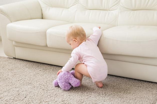 Девочка играет возле дивана дома