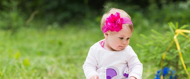 緑の芝生で遊ぶ女の赤ちゃん、家族のピクニックのクローズアップ。