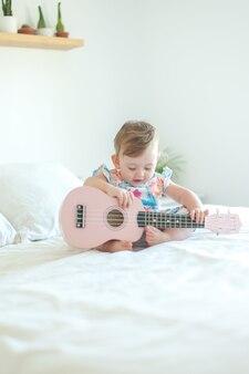 우쿨렐레를 연주하는 아기 소녀