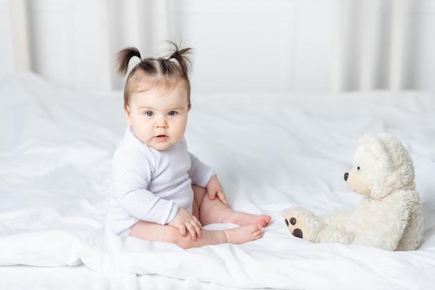 自宅のベッドでテディベアのおもちゃで遊ぶ女の赤ちゃん、遊びの概念と子供の発達