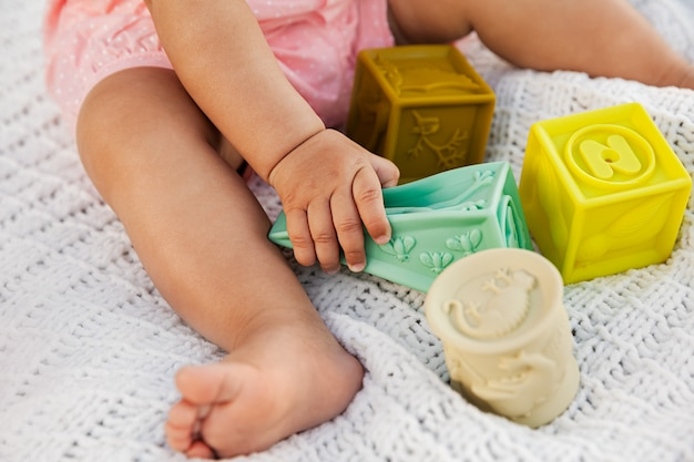 Baby girl playing with colorful rubber blocks on white knitted blanket outdoor at natural light