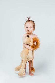 흰 벽에 고립 된 그녀의 사자 장난감을가지고 노는 아기 소녀.
